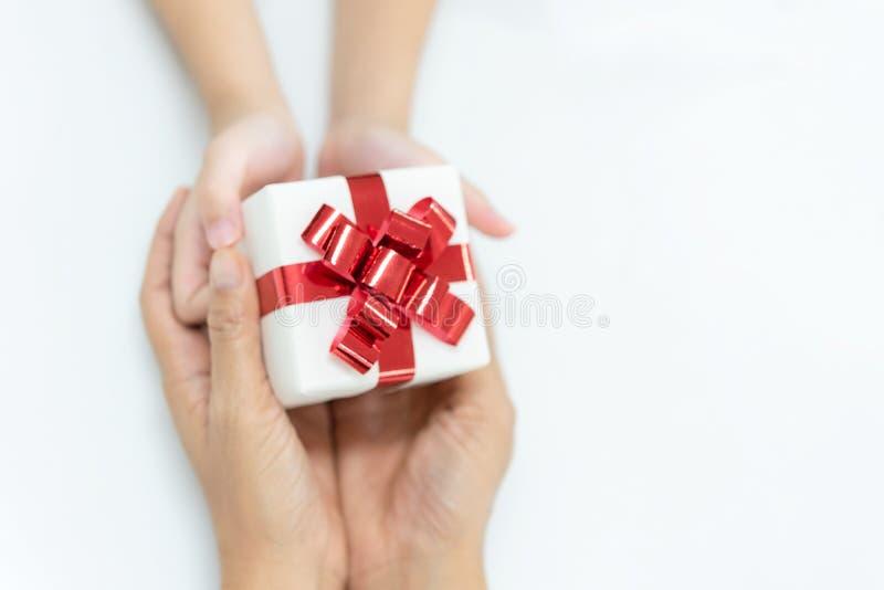 De dochter geeft een gift aan moeder Witte doos met rode boog in de de meisjeshanden en moeder royalty-vrije stock foto's