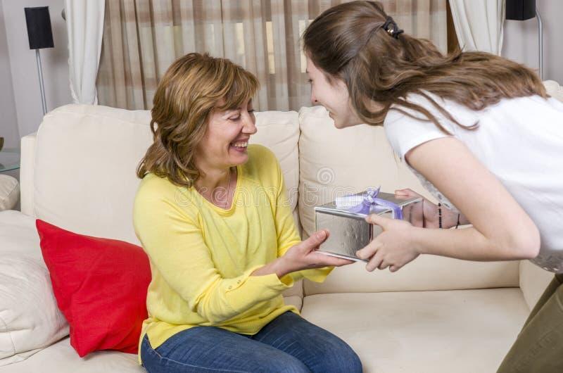 De dochter geeft een gift haar moeder in de Moeder` s dag stock foto