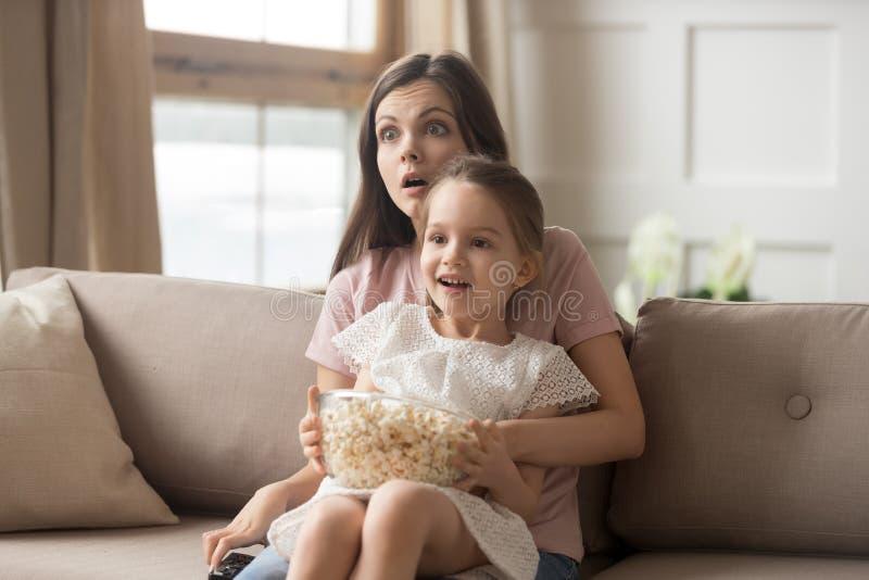 De dochter van de moedergreep op overlapping het letten op film voelt geschokt royalty-vrije stock foto
