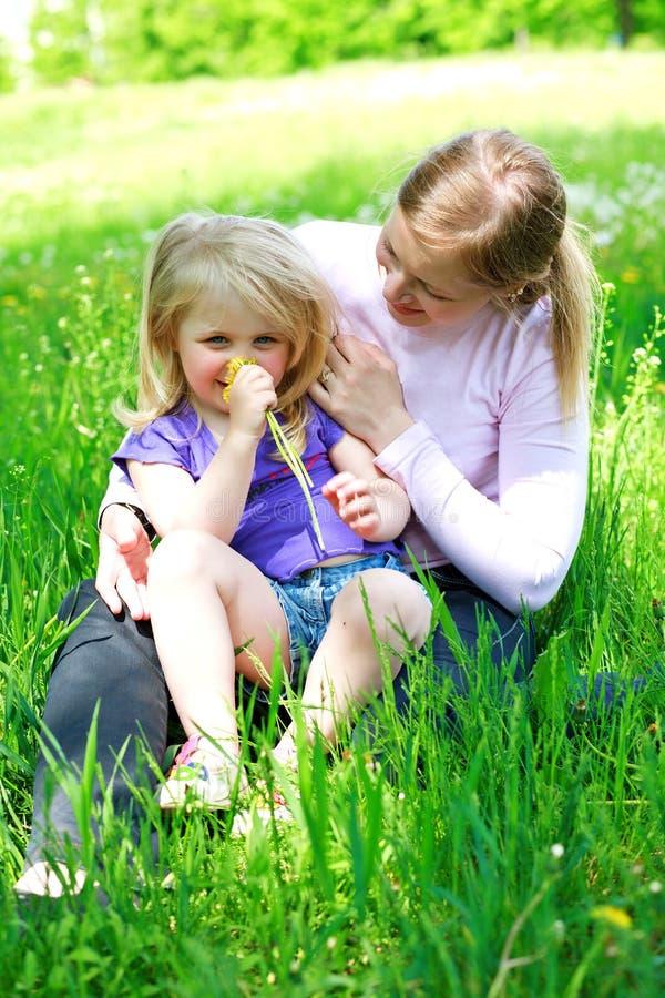 De dochter zit in openlucht op moeder op een gras stock foto