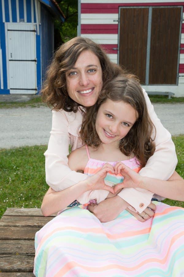De de dochterfamilie van de moederliefde maakt in openlucht hart met hand royalty-vrije stock foto's