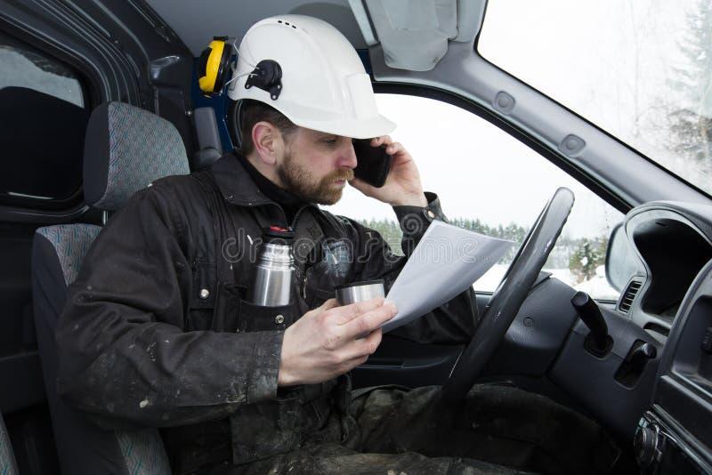 De documenten die van de bouwvakkerlezing, die een auto drijven en op de telefoon spreken terwijl het drinken van koffie in Finla royalty-vrije stock foto's