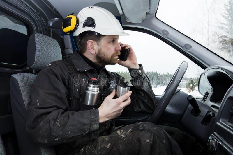 De documenten die van de bouwvakkerlezing, die een auto drijven en op de telefoon spreken terwijl het drinken van koffie in Finla stock foto's