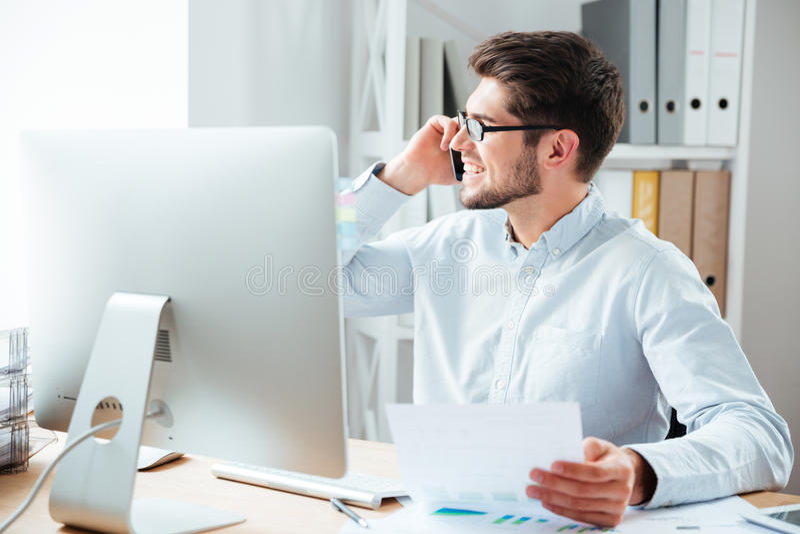 De documenten van de zakenmanholding en het spreken op mobiele telefoon in bureau stock foto's