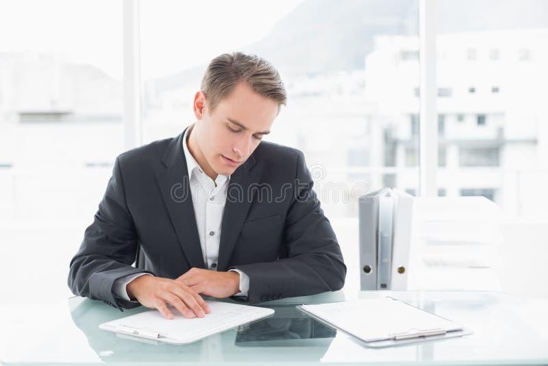 De documenten van de zakenmanlezing bij bureau stock afbeeldingen