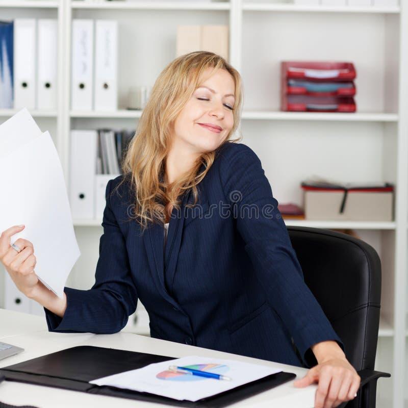 De Documenten van onderneemsterfanning herself with bij Bureau stock afbeeldingen