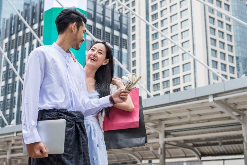 De dollarcontant geld van de zakenmanholding met laptop en Aziatische vrouwengreep royalty-vrije stock foto