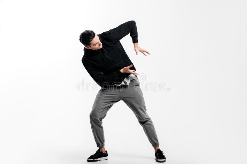 De donker-haired jonge mens die een zwart sweatshirt en een grijze broek dragen is het dansen straatdans Hij maakt gestileerde be royalty-vrije stock afbeelding