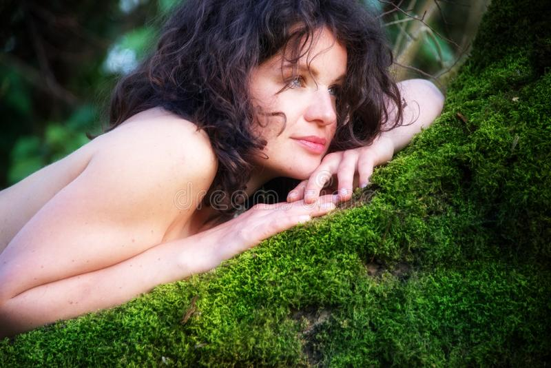 De donker-haired jonge sexy vrouw ligt gelukkig tevreden in een oude wilg op het groene mos met naakte schouders en glimlach stock afbeeldingen