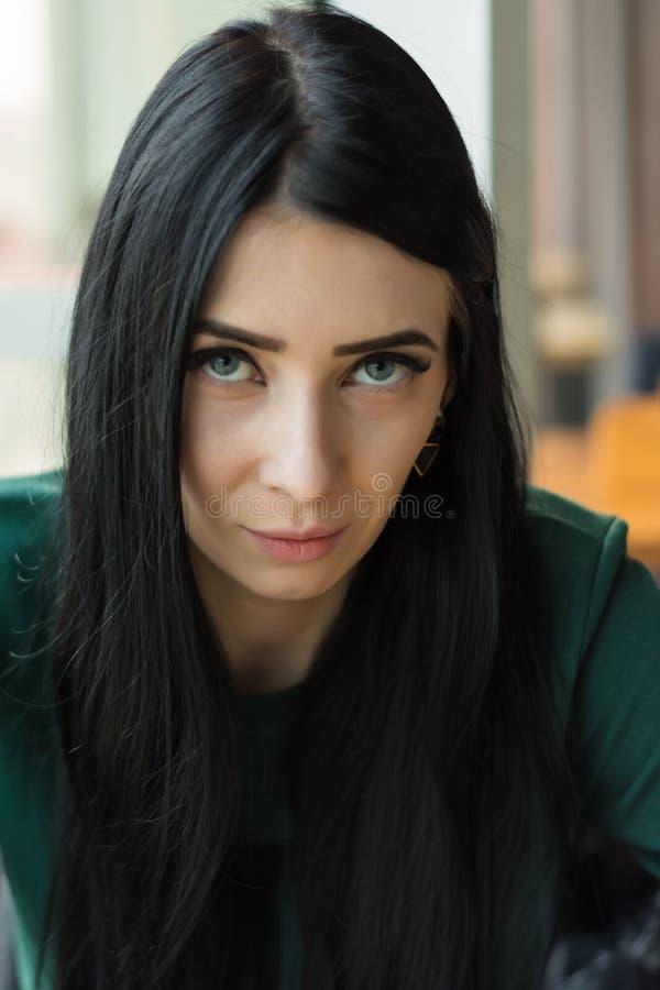 De donker-haired jonge vrouw met sluw, provocatief, het flirten kijkt stock fotografie