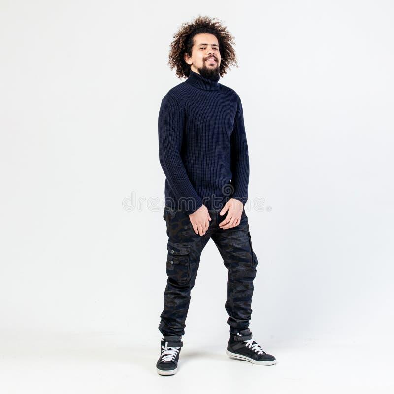 De donker-haired krullende kerel met een baard in een zwarte col, een kaki broek en tennisschoenen stelt in de studio op het wit royalty-vrije stock afbeeldingen