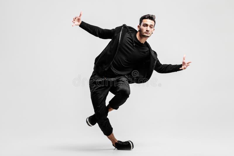De donker-haired modieuze jonge mens die een zwart sweatshirt en een zwarte broek dragen maakt gestileerde bewegingen van straatd stock foto