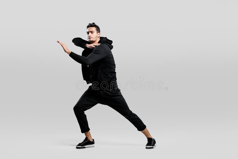 De donker-haired modieuze jonge mens die een zwart sweatshirt en een zwarte broek dragen maakt gestileerde bewegingen van straatd royalty-vrije stock afbeelding