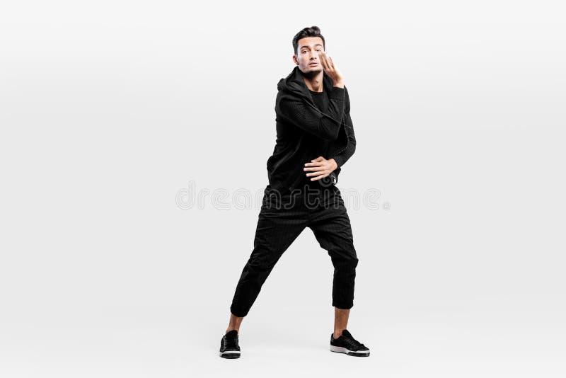 De donker-haired modieuze jonge mens gekleed in modieuze zwarte kleren is het dansen straatdansen Hij maakt gestileerde beweginge royalty-vrije stock afbeeldingen