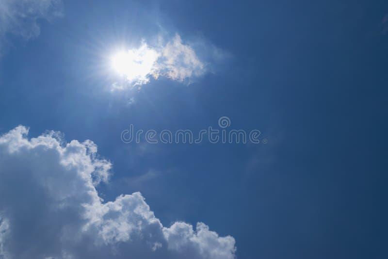 De donkerblauwe hemel met witte wolken als voorgrond en su stock afbeelding