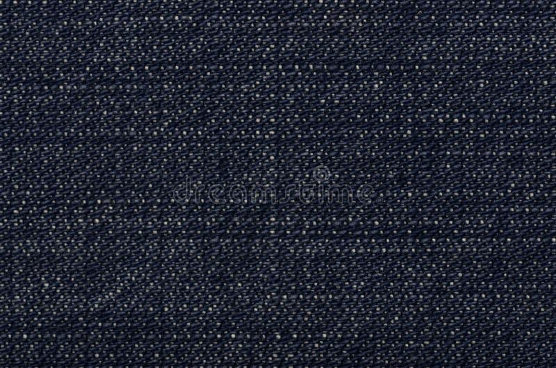 De donkerblauwe textuur van denimjeans met verdwijnt langzaam en verbleekt stock foto