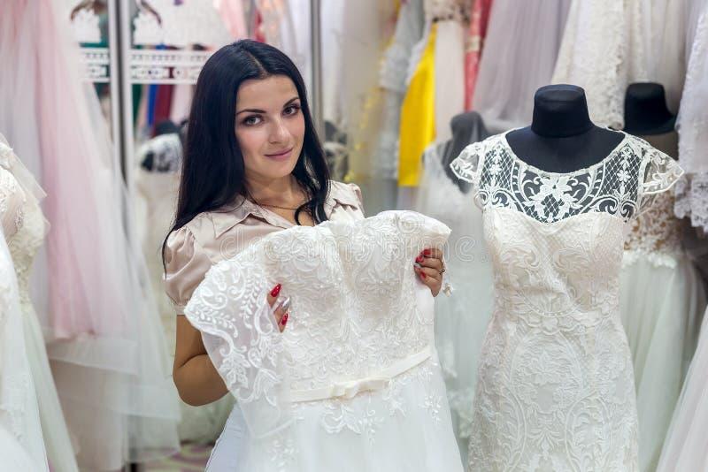 De donkerbruine bruid probeert op huwelijkskleding in salon royalty-vrije stock fotografie