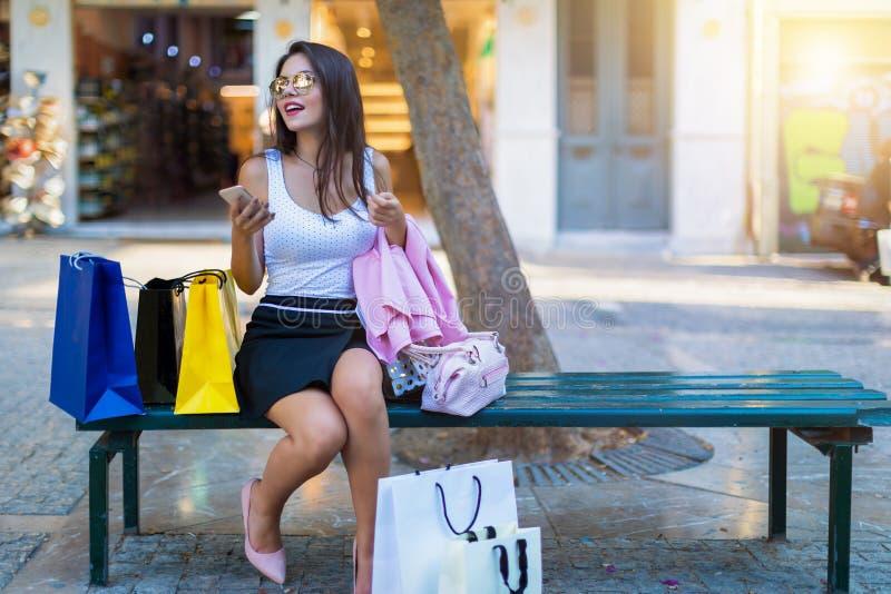 De donkerbruine die vrouw zit op een bank door het winkelen zakken wordt omringd royalty-vrije stock afbeeldingen