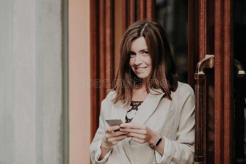 De donkerbruine vrolijke mooie brief van vrouwenteksten e-mail, gebruiks mobiele telefoon en vrije Internet-verbinding, gekleed i royalty-vrije stock foto