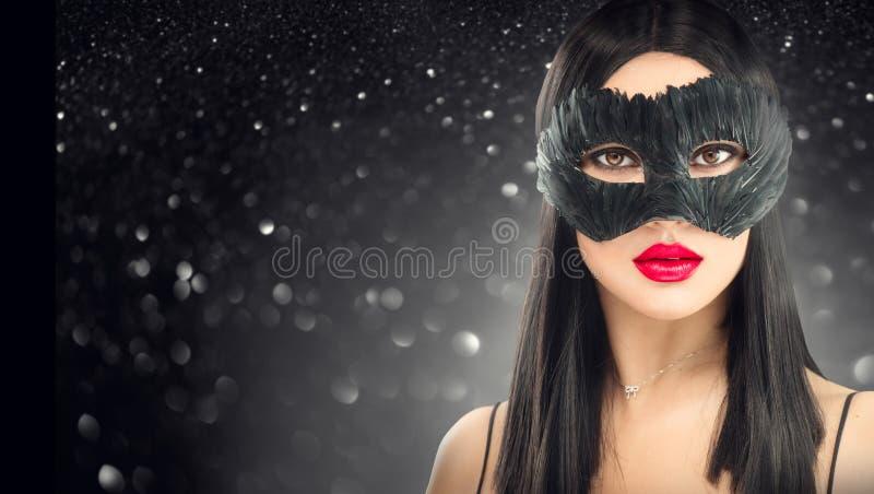 De donkerbruine vrouw die van de schoonheidsglamour het donkere masker van Carnaval, partij over vakantie zwarte achtergrond drag stock foto's