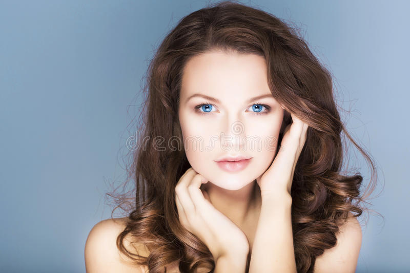 De donkerbruine vrouw met blauwe ogen zonder maakt omhoog, natuurlijke onberispelijke huid en handen dichtbij haar gezicht stock foto's