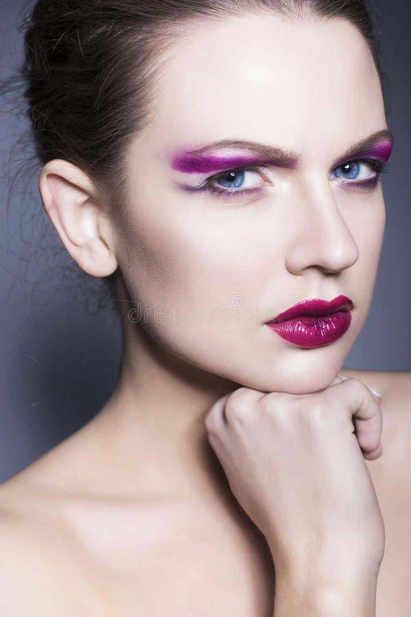 De donkerbruine vrouw met creatief maakt omhoog tot violette oogschaduwwen volledige rode lippen, blauwe ogen en krullend haar me stock fotografie