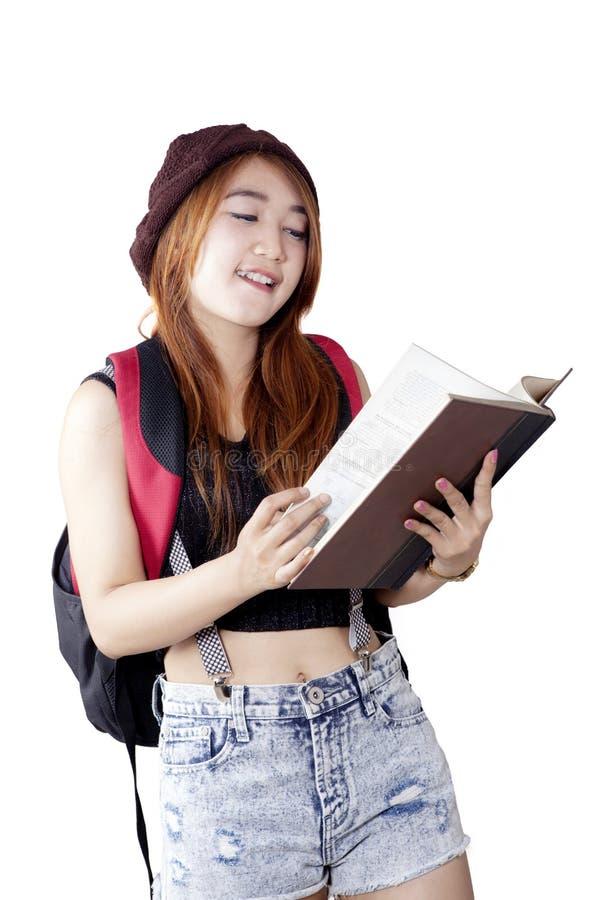 De donkerbruine vrouwelijke student leest boek in studio stock foto