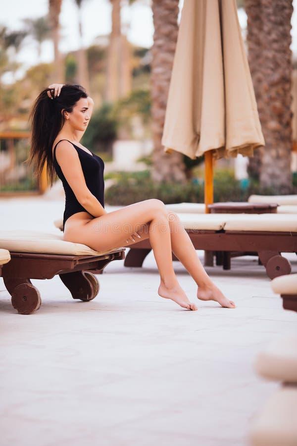 De donkerbruine Vrouwen dragen hoedenzitting op comfortabele stoel in pool op de zomerroeping stock fotografie