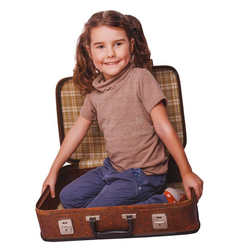 De donkerbruine zitting van de meisjesbaby in een koffer voor geïsoleerde reis royalty-vrije stock fotografie