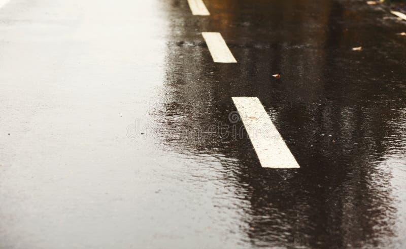 De donkere grijze achtergrond van de asfaltweg nat na regen stock foto's