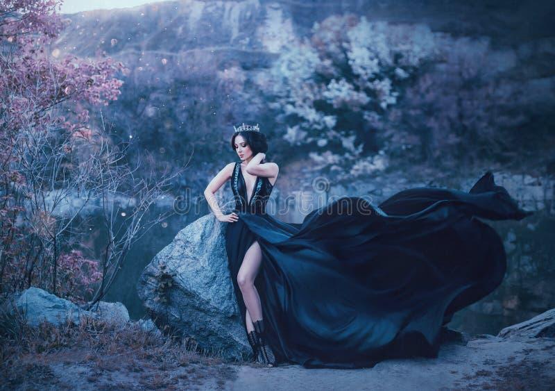De donkere koningin stelt tegen de achtergrond van sombere rotsen Een luxueuze zwarte kleding met een lange trein die in fladdere royalty-vrije stock foto's