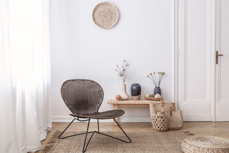 De donkere, moderne rieten stoel in een wit woonkamerbinnenland met een houten bank en de decoratie maakten van natuurlijke mater royalty-vrije stock afbeeldingen