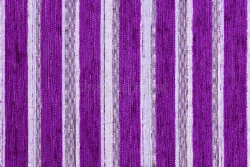 De donkere purpere verticale van het de stoffenclose-up van de strepen synthetische geweven stoffering textuur en de achtergrond stock foto