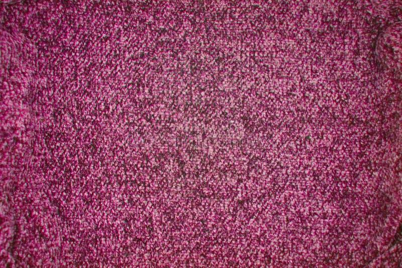 De donkere roze gebreide achtergrond van het textuurpatroon stock foto