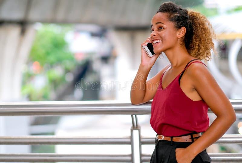 De donkere tan huid mengde rasvrouw met het glimlachen vraag aan iemand en bespreking met haar mobiele telefoon, ook tribune de g stock foto