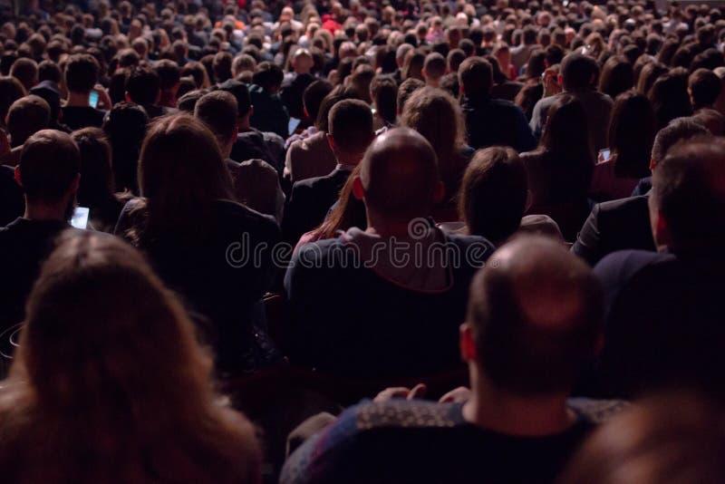 In de donkere zaal is er een mening van de rug van een menigte van honderden mensen die en op het scherm in een bioscoop zitten l stock foto