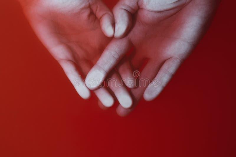 De doorweven mannelijke en vrouwelijke handen drukten aan het glas in rood water, het concept liefde en pijn royalty-vrije stock fotografie