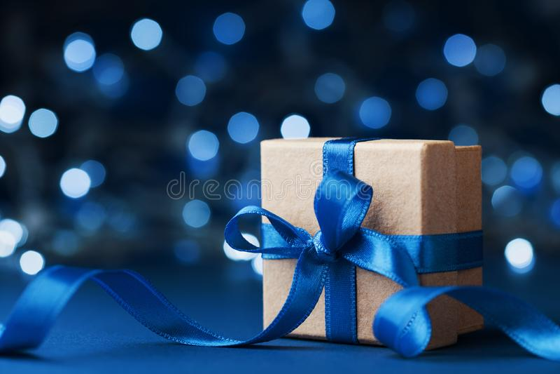De doos of het heden van de vakantiegift met booglint tegen blauwe bokehachtergrond De magische kaart van de Kerstmisgroet royalty-vrije stock foto