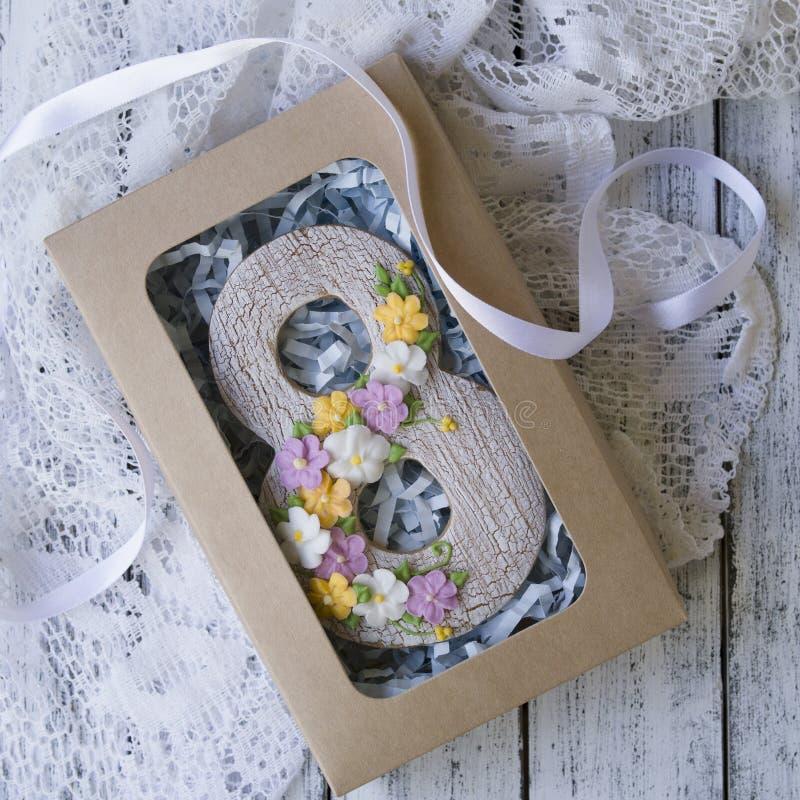 De doos met Koekje met glans wordt behandeld in vorm van nummer acht met de lente wordt gemaakt bloeit op witte houten achtergron royalty-vrije stock afbeeldingen