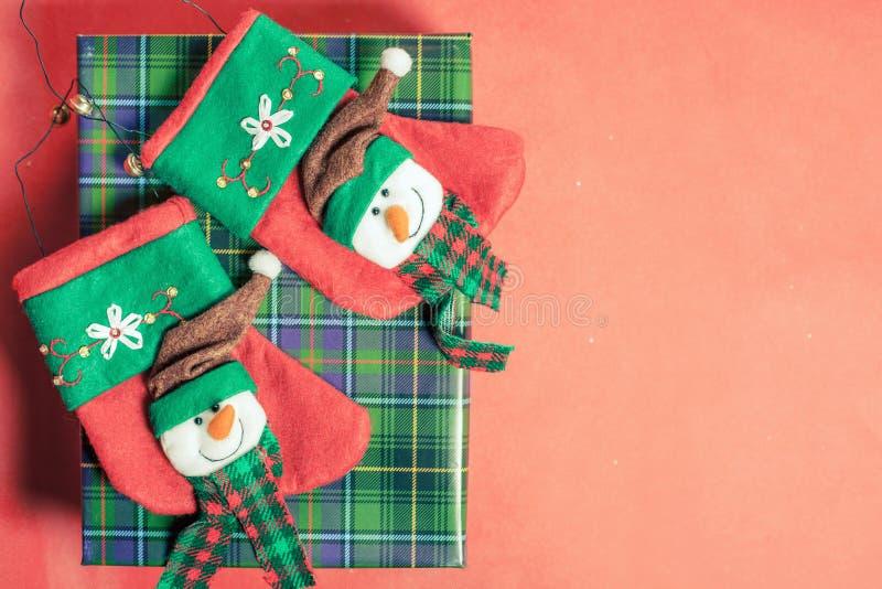 De doos van de Kerstmisgift bij rode achtergrond met sokken voor heden stock foto's