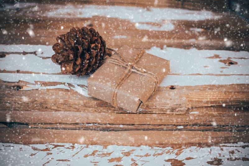 De doos van de Kerstmisgift en een denneappel op uitstekende houten achtergrond, met dalende gestemde sneeuw, stock foto's