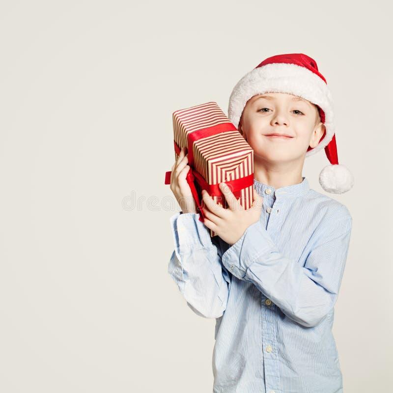 De Doos van de Kerstmisgift van de jong geitjeholding Kindjongen en Gift royalty-vrije stock foto's