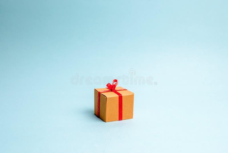 De doos van de gift op blauwe achtergrond minimalism De benadering van de de Nieuwjaarvakantie of verjaardag Verkoop van giften,  royalty-vrije stock afbeelding