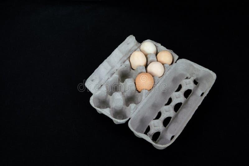 De doos van het kartonei met vijf eieren op zwarte matachtergrond stock fotografie