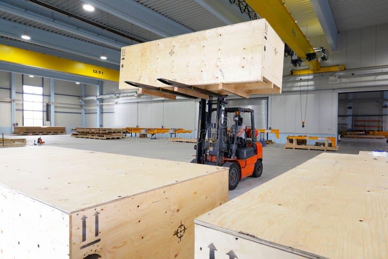 De doos van het vorkheftruckvervoer in een industriële onderneming voor opslag stock afbeeldingen