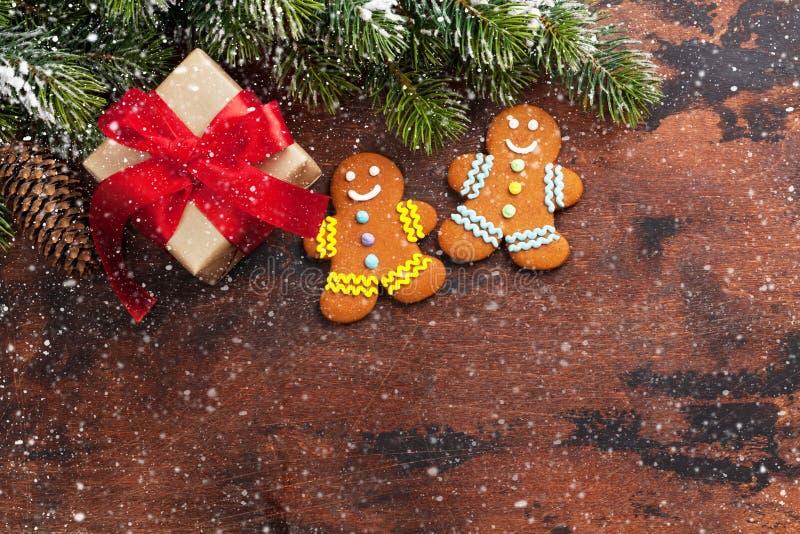 De doos van de Kerstmisgift, peperkoekkoekjes en sparrentak door sneeuw op houten achtergrond wordt behandeld die De hoogste acht stock foto's
