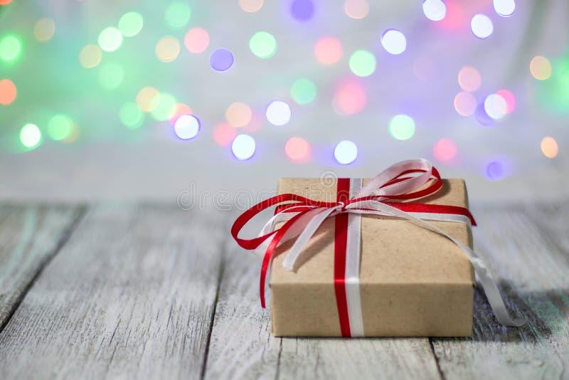 De doos van de Kerstmisgift tegen bokehachtergrond De groetkaart van de vakantie stock foto