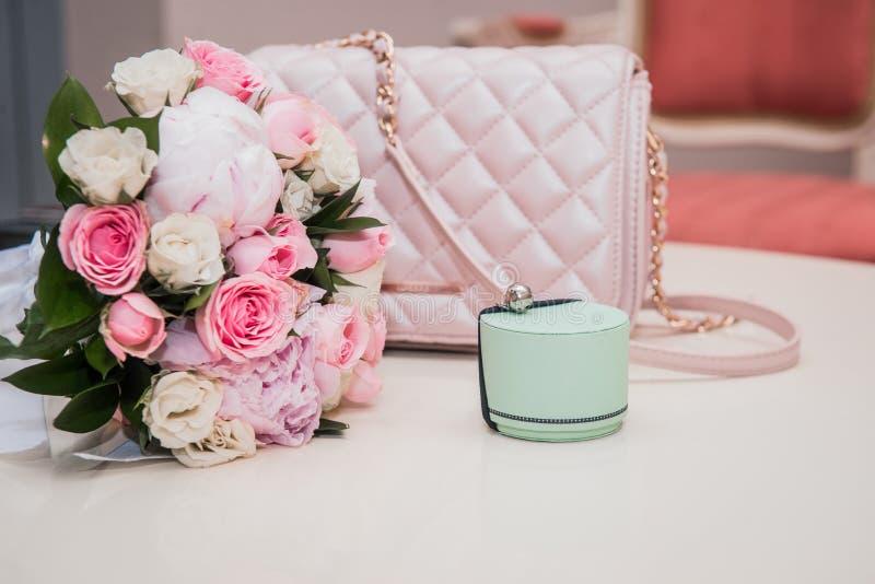 De doos van de muntring, huwelijksboeket van roze rozen en pioenen, roze handtas stock fotografie