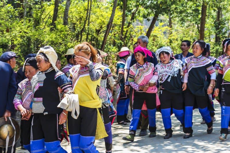 De dorpsbewoners die van de Haniminderheid huis na een begrafenisoptocht terugkeren stock afbeelding