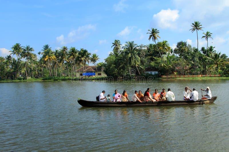 De dorpsbewoners reizen in een traditionele boot in de binnenwateren stock foto